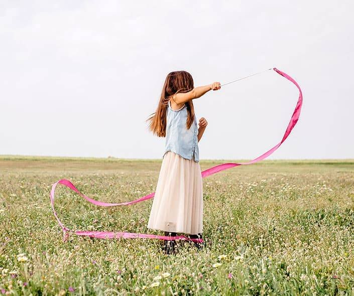 girl playing with dancing ribbons