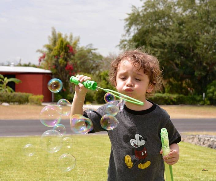 image of boy playing with soap bubbles