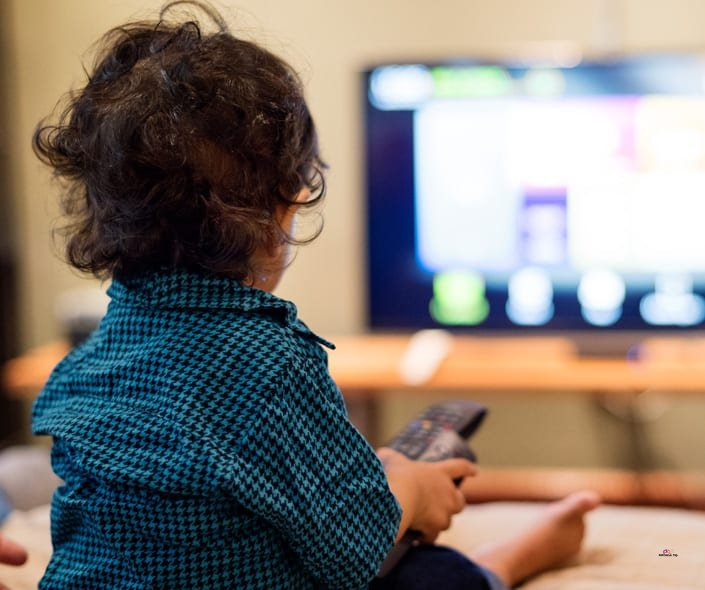 Image of young boy watching educational cartoons
