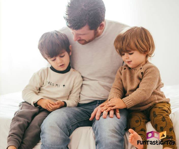 Image of father talking to sons on bed