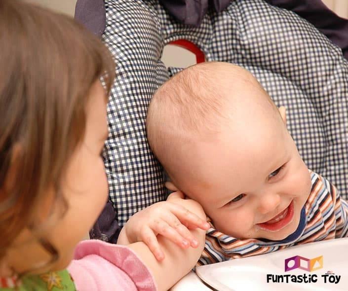 Image of girl tickling smiling baby