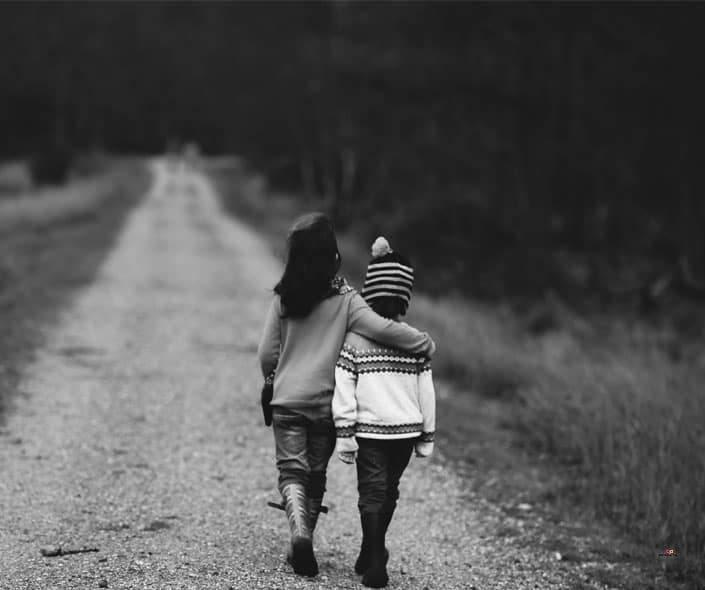 Image of little girl hugging boy on road
