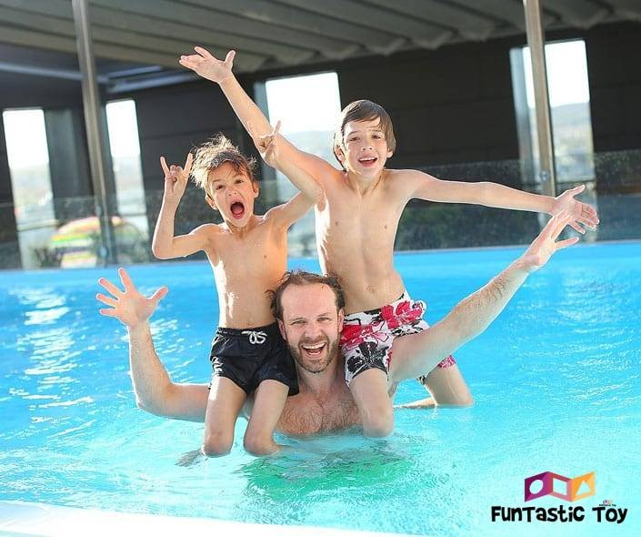 Image of happy two boys on fathers shoulders in pool