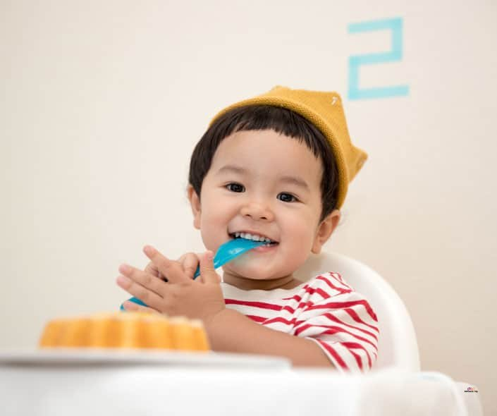Featured image of cute toddler eating birthday cake
