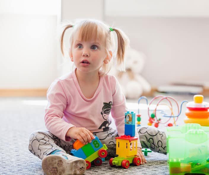 Featured image of little girl with ADHD playing with toys on floor