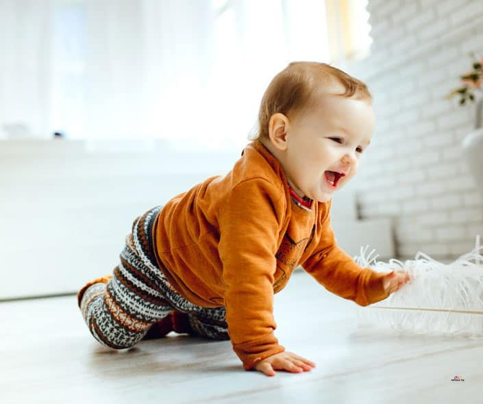 Featured image of smiling baby crawling on floor