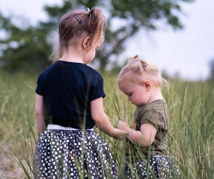 Featured image of two little girls standing in grass field
