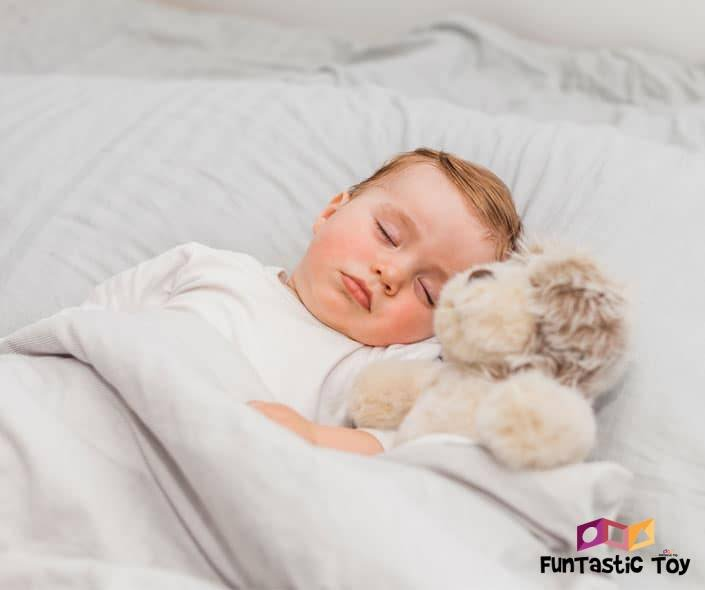 Image of baby boy with stuffed toy sleeping