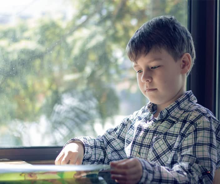 Image of boy scrolling book next to window