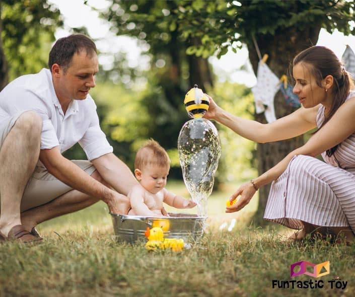 Image of mother and father bathing baby in park