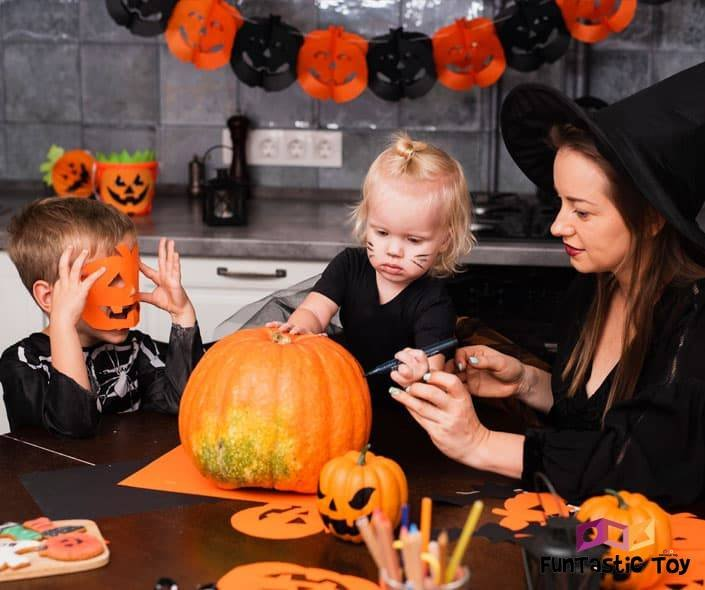 Image of mother and two children carving pumpkin on halloween
