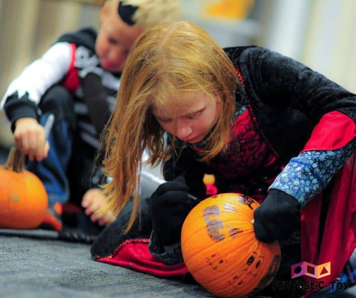 Image of two boys in costumes decorating pumpkins