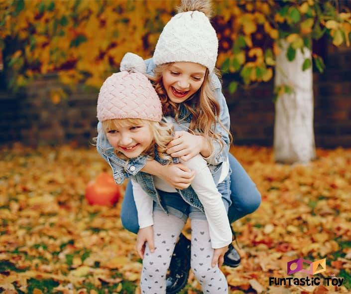 Image of two girls playing in autumn park