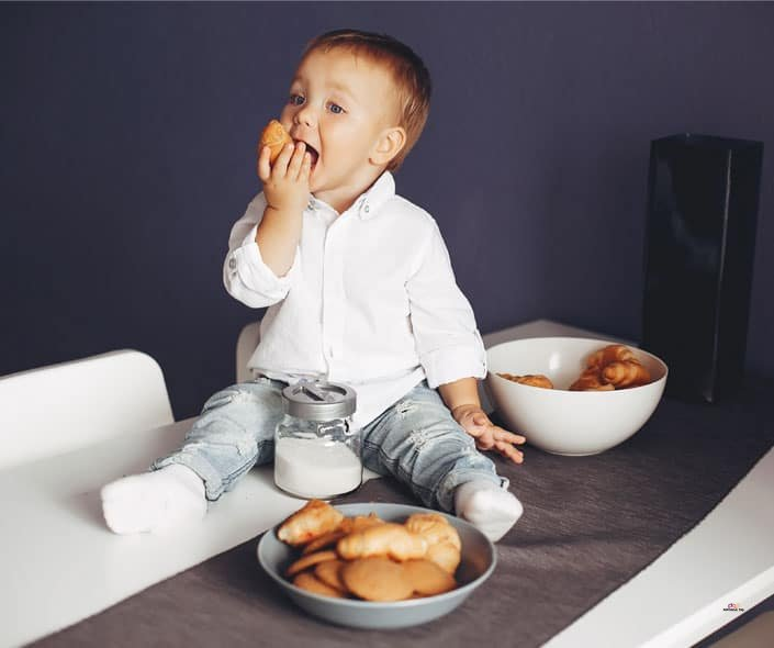 Featured image of baby boy eating pastery on table