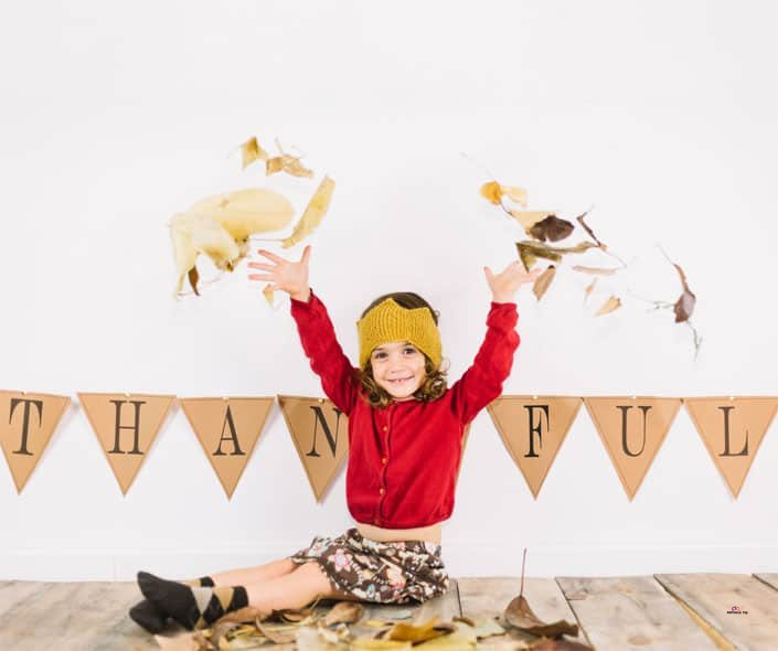 Featured image of smiling girl in red throwing leaves on thanksgiving