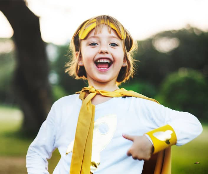 Featured image of smiling girl in white and yellow superhero costume