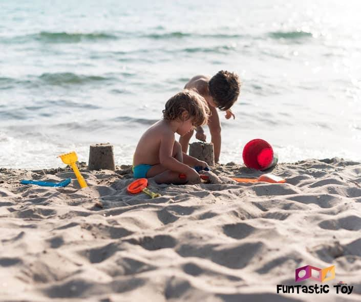 Iimage of two boys making sandcastles at the beach