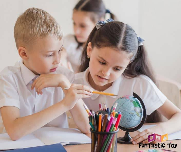 Image of boy and girl in school looking at globe
