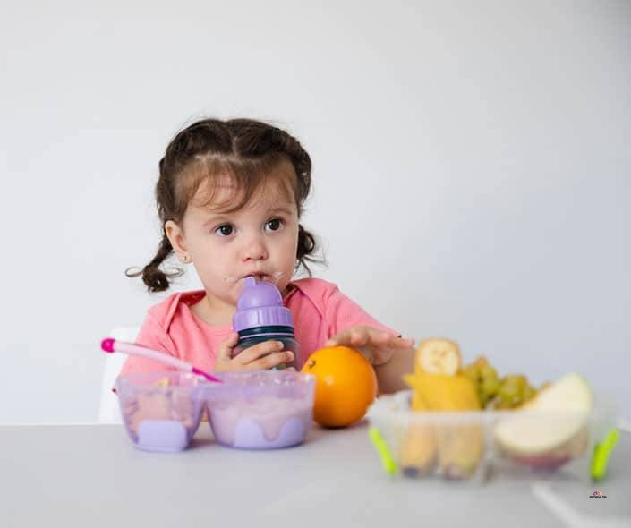 Image of cute girl at table with fruit and baby food
