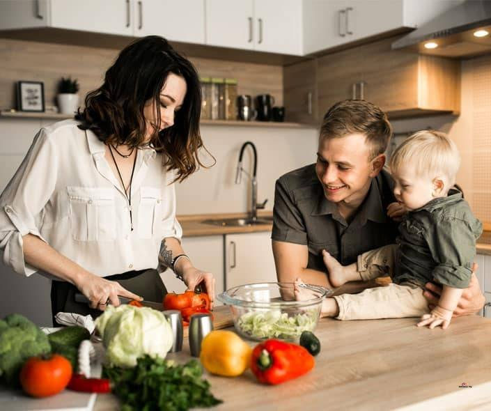 Image of family with baby in kitchen with vegetables