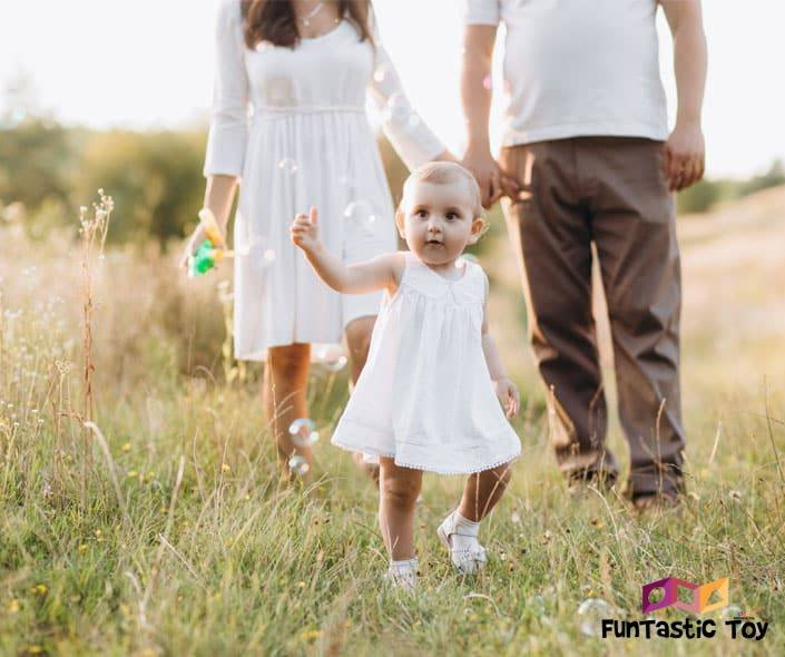Image of little girl in white walking in field with parents behind