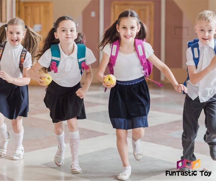 Image of schoolkids running holding apples