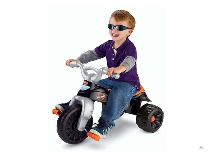 Image of smiling boy riding Fisher Price Harley Davidson Trike