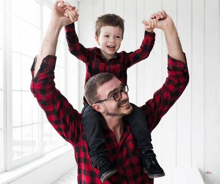 Featured image of father carrying son on shoulders with raised arms