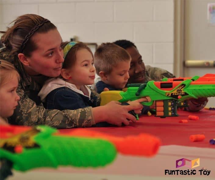 Image of soldiers teaching children to shoot nerf guns