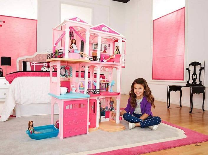 Image of cute girl playing with Barbie Dreamhouse