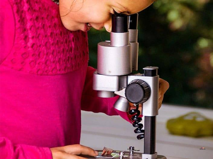 Image of girl using National Geographic Microscope Set